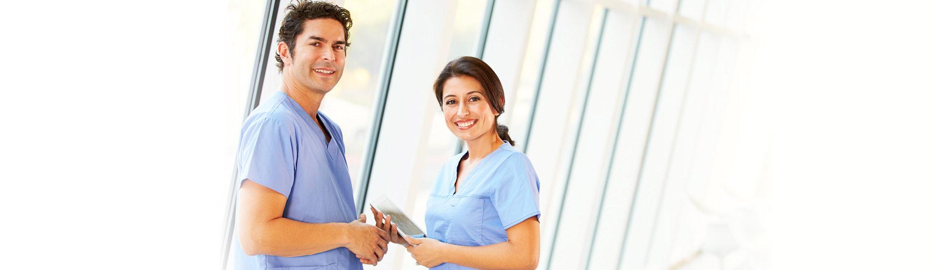 portrait of two nurses smiling through the camera